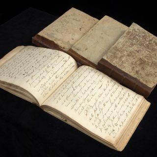 Four manuscript orderly books from the Revolutionary War, one open with handwriting filling the pages and three others closed beside it
