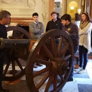 Evan Phifer explains a cannon to teachers at the American Revolution Institute headquarters.