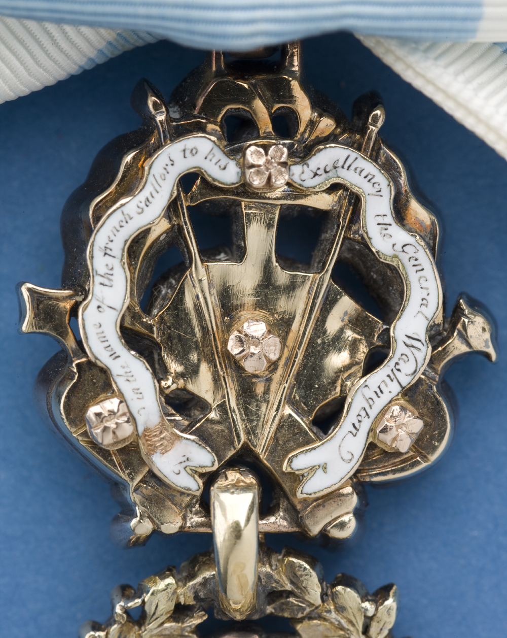 Back side of the gold trophy of a medal with an inscription on a white enamel ribbon