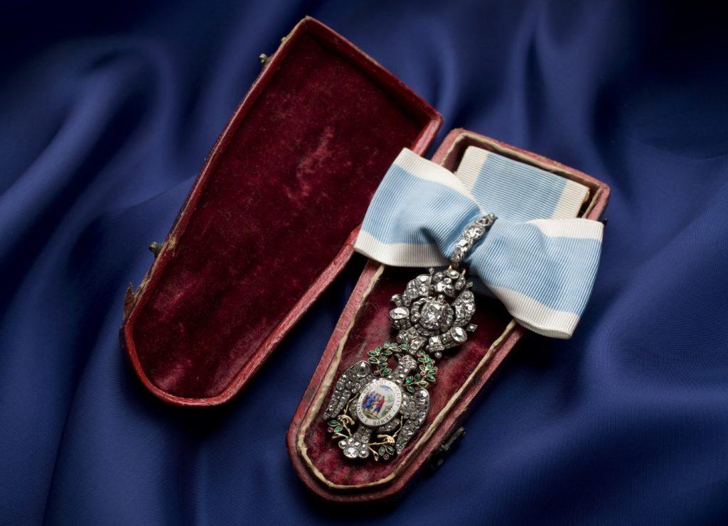 Bejeweled insignia resting inside a red velvet-lined case
